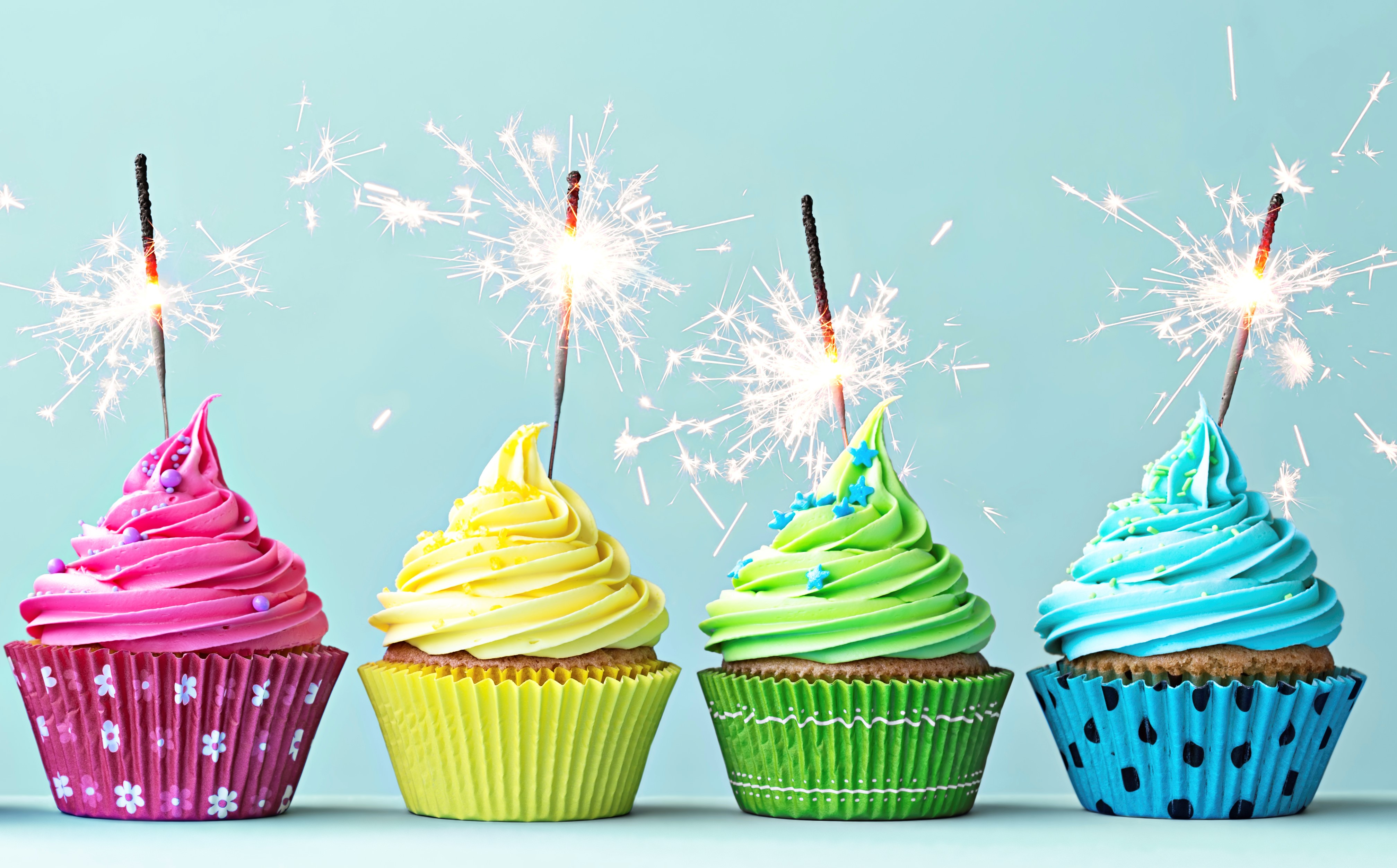 Row of colorful cupcakes with sparklers